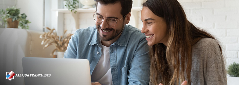Couple smiling looking at the benefits of investing in a franchise on a laptop