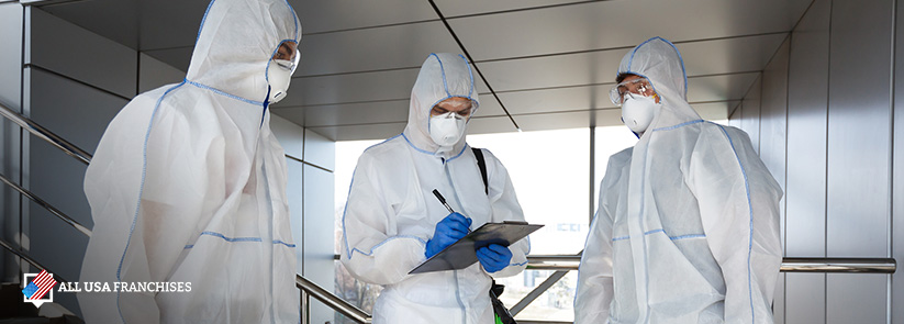 three men with protective gear sanitizing