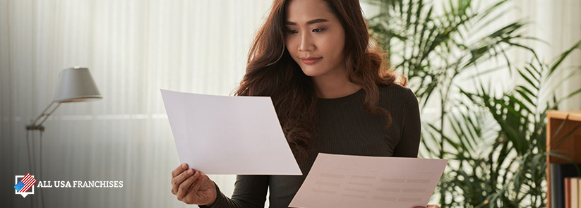 Franchisee Woman Comparing Franchise Rights Document vs. Franchise Agreement Document